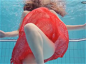red dressed teenager swimming with her eyes opened